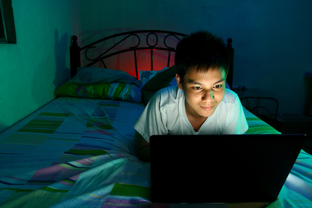Teenager using his computer at night in bed.
