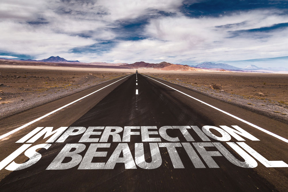 "A road with the words ""Imperfection is Beautiful""."