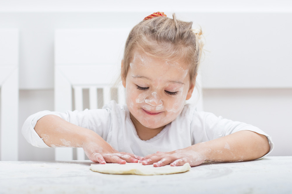 Young girl kneading and playing with dough.